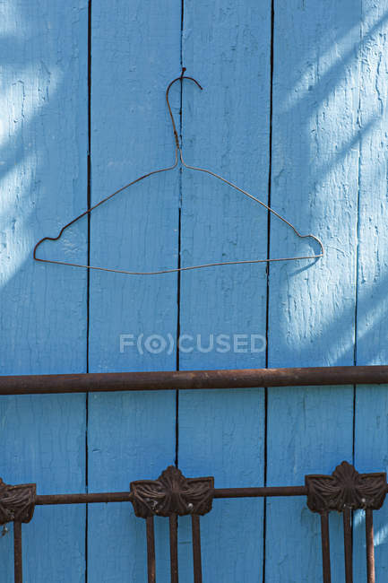 Вешалка для пальто пустой проволоки на синий забор — стоковое фото