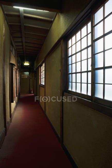 Vista interior do gasto corredor com tapete vermelho — Fotografia de Stock