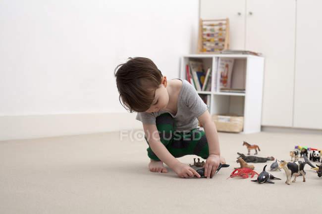 Маленький хлопчик грає з іграшкою фігурки тварин на поверсі спальня — стокове фото