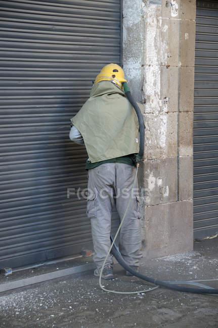 Vista traseira do trabalhador muro de pedra para jato de areia — Fotografia de Stock