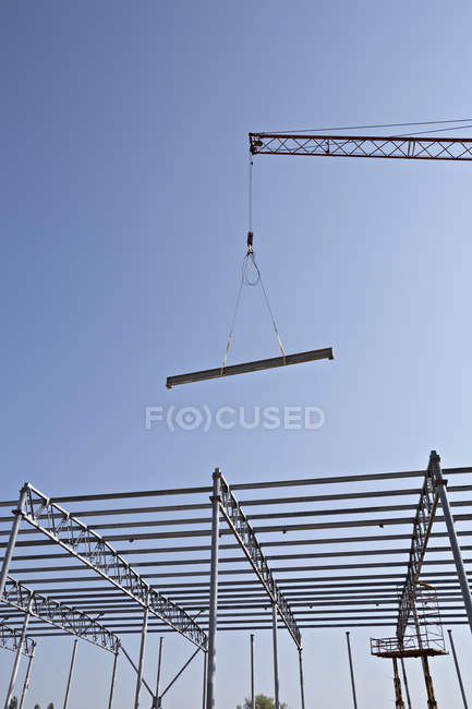 Crane lowering steel beam towards construction frame — Stock Photo
