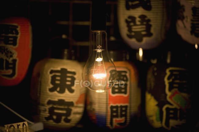 Leuchtende Glühbirne über japanische Papierlaternen — Stockfoto