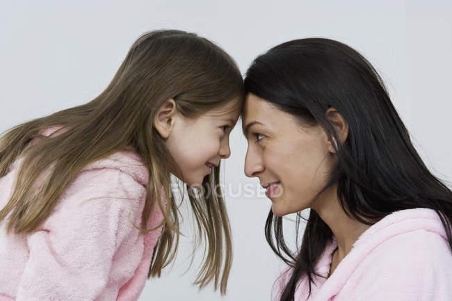 Una madre y una hija con rosa albornoz - foto de stock