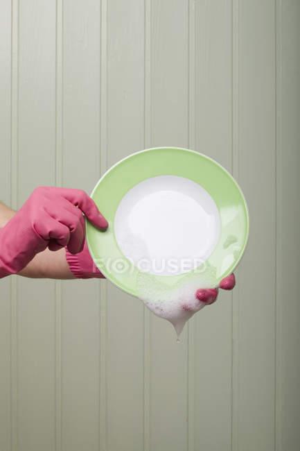 Detalle de una persona que usa guantes de goma y sostiene un plato limpio - foto de stock