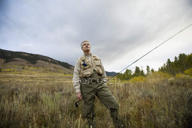 Man standing in nature with fly rod and looking up — Stock Photo