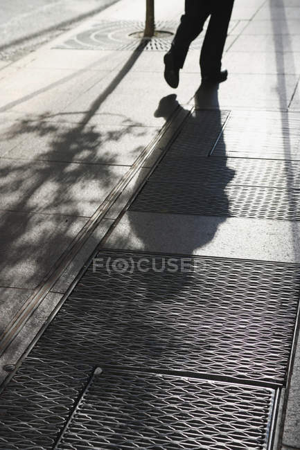 Shadow of person walking along street on sunny day — Stock Photo