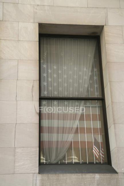 Bandera americana refleja en ventana con cortina - foto de stock