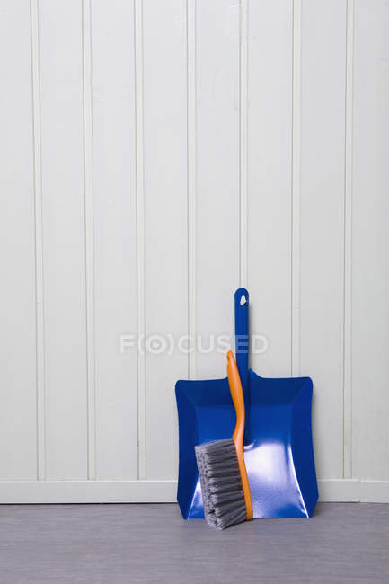 Close up view of dustpan and broom leaning on wall — Stock Photo