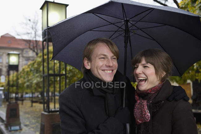 Jeune couple riant sous un parapluie — Photo de stock
