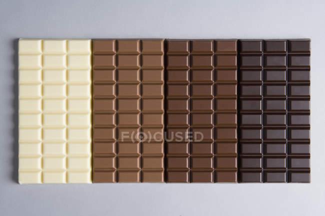 Ряд різних Шоколадки на сірий фон — стокове фото