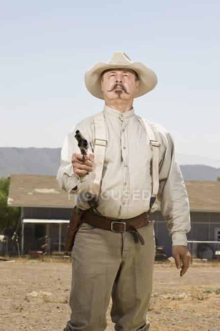 Retrato de um vaqueiro, apontando sua arma — Fotografia de Stock