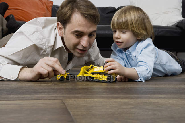 A father and son playing with toy trucks — Stock Photo