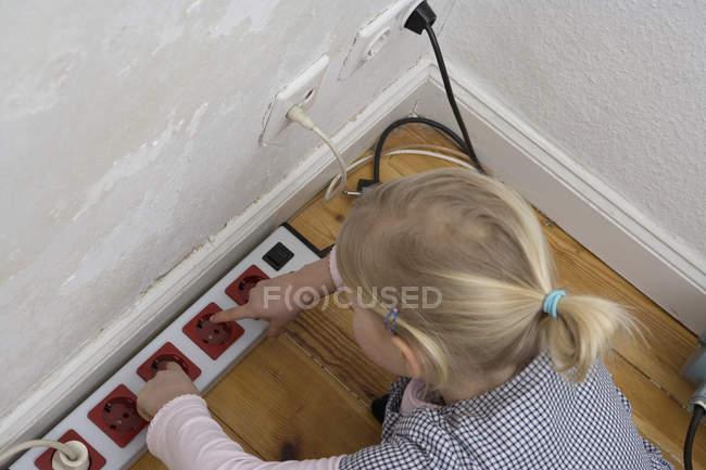 Una giovane ragazza che tocca una presa elettrica — Foto stock