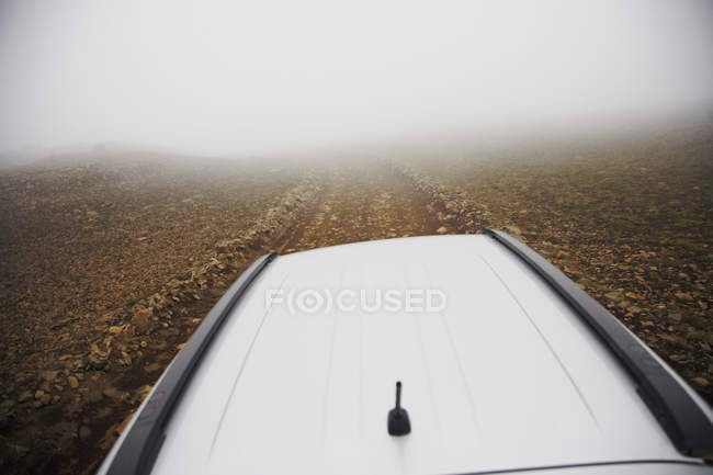 Over head view of car moving on foggy road at countryside — Stock Photo