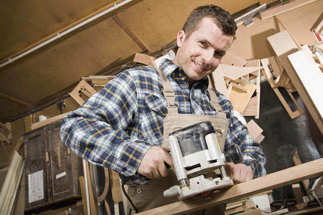 Carpenter using sanding machine in workshop — Stock Photo