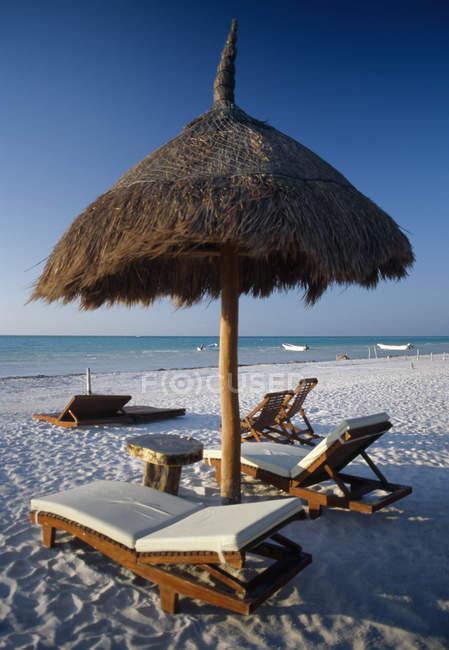 Sdraio e ombrellone in paglia sulla spiaggia — Foto stock