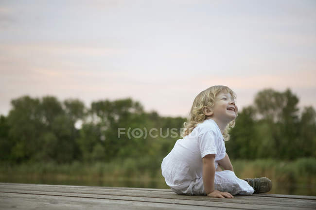 Смеющийся Мальчик сидит на пристани — стоковое фото
