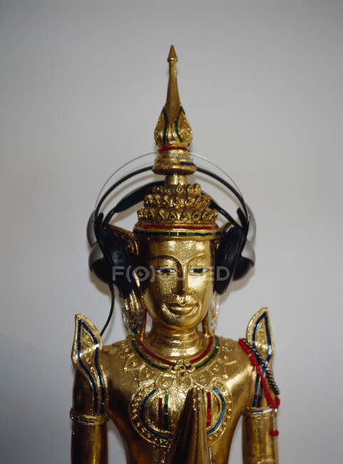 Crop gold Buddha statue with headphones — Stock Photo