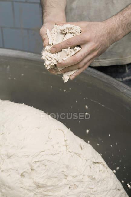 Crop boulanger pétrissant la pâte sur le bol — Photo de stock