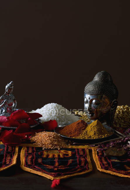 Still life of typical Indian cuisine ingredients and Buddha statues — Stock Photo