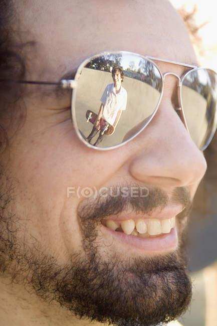 Крупный план скейтбордиста, отраженный в очках друзей — стоковое фото