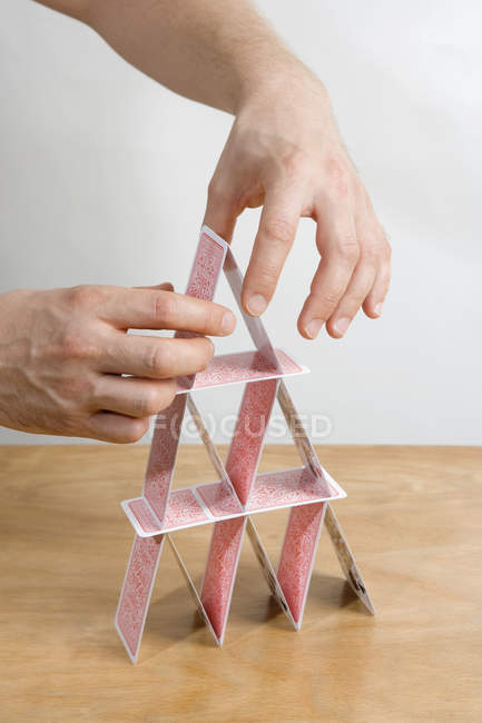 Crop manos masculinas haciendo casa de naipes - foto de stock
