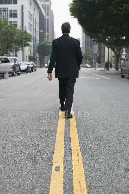 Rear view of businessman walking along dividing line on city street — Stock Photo