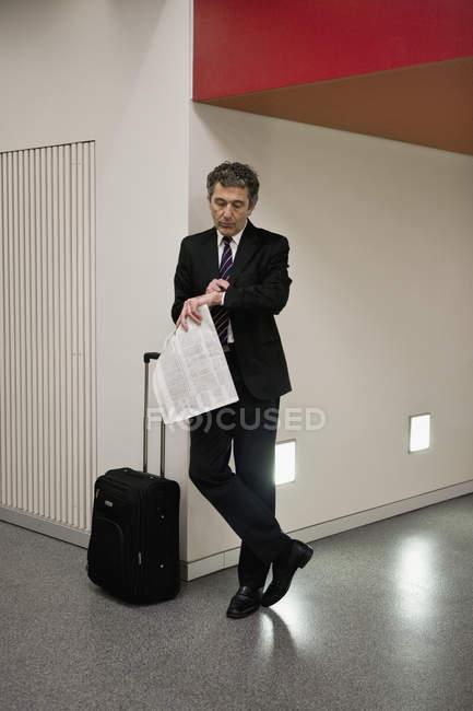 Бизнесмен с чемоданом и газетой в руках. — стоковое фото