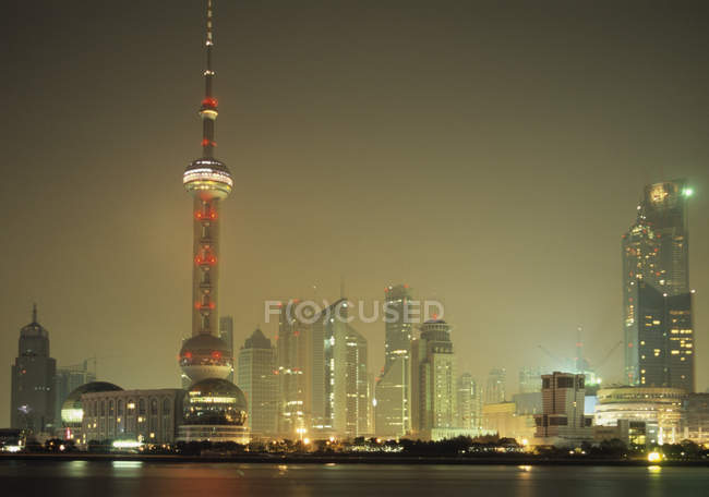Night cityscape of illuminated skyscrapers and TV tower in dusk — Stock Photo