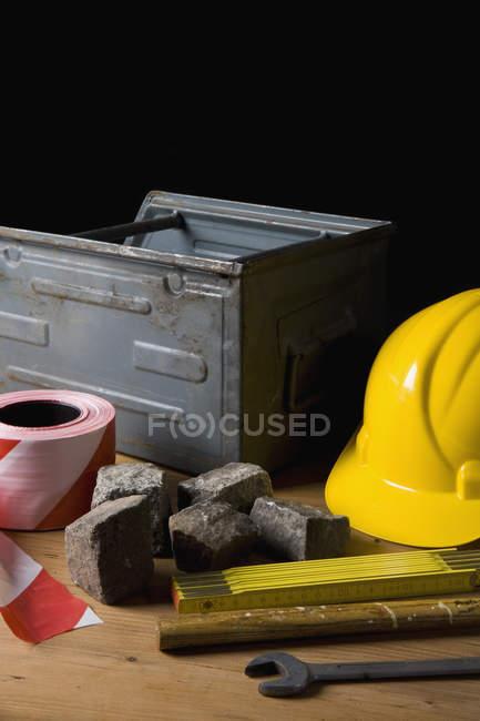 Still life of masonry equipment on table over black background — Stock Photo