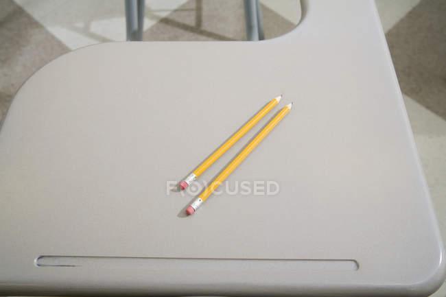 Two pencils on empty school desk — Stock Photo