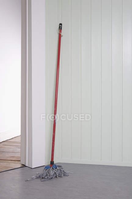 Common mop leaning on room corner — Stock Photo