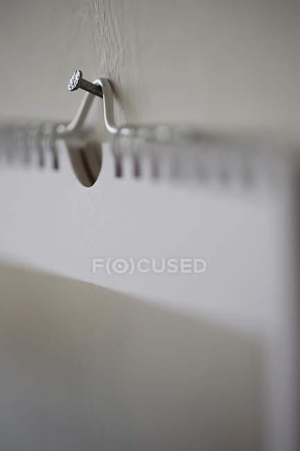 Close up vista de prego segurando livro espiral — Fotografia de Stock