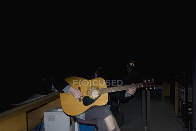 Obscured person in shadow playing guitar — Stock Photo