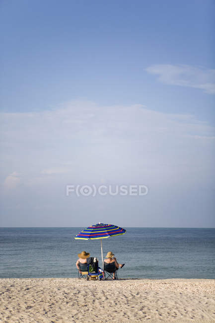 Two people sitting on beach and admiring seascape — Stock Photo