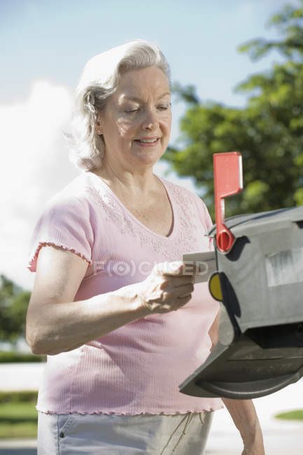 A senior woman checking the mailbox — Stock Photo
