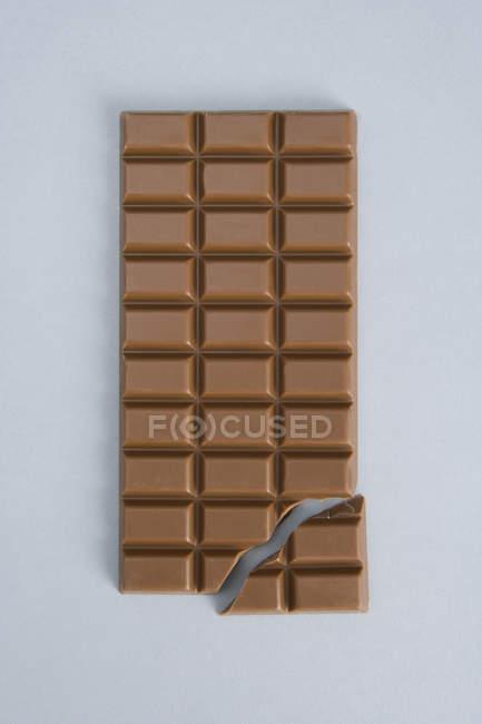 Vue directement au-dessus de la barre de chocolat cassée sur fond blanc — Photo de stock