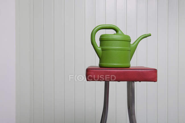 Plastic watering can on stool over white wall — Stock Photo