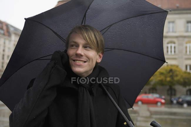 Jeune homme utilisant un téléphone portable et tenant un parapluie — Photo de stock
