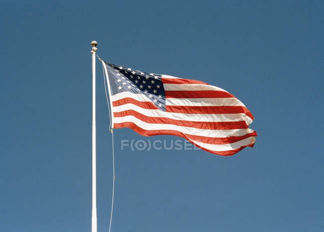 Зніміть американський прапор ляскаючі проти синього неба — стокове фото