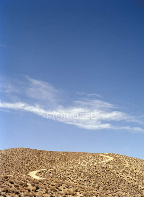 Winding road on desert hill's slope over bright sky — Stock Photo