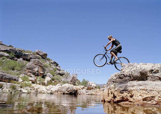 Um homem a saltar de uma bicicleta de montanha em um fluxo — Fotografia de Stock