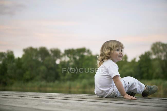 Un ragazzo sorridente che si siede su un molo — Foto stock