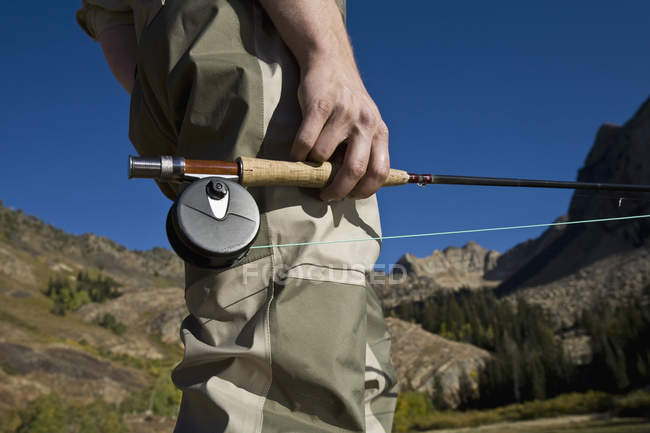 Midsection of man holding fly rod — Stock Photo