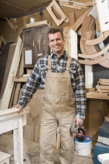 Portrait d'un charpentier souriant debout dans un atelier — Photo de stock