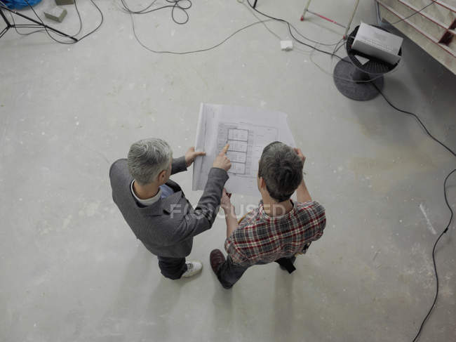 Overhead view of construction worker going over blueprints with architect — Stock Photo