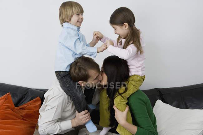 Due genitori che portano i bambini sulle spalle e si baciano — Foto stock