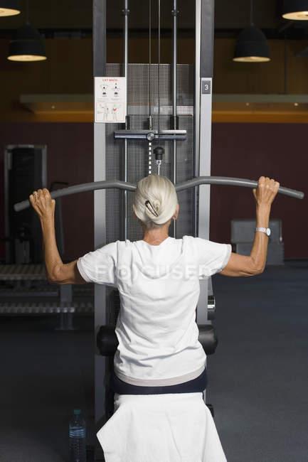 Rückansicht des grauen Haaren Frau mit seitlichen Pulldown-Gewicht Maschine — Stockfoto