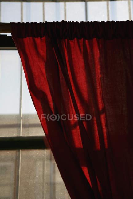 Luz solar brillando a través de la ventana sobre la cortina roja - foto de stock