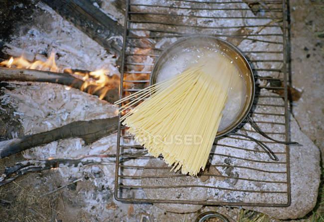 Vista dall'alto degli spaghetti in pentola bollente sul falò — Foto stock